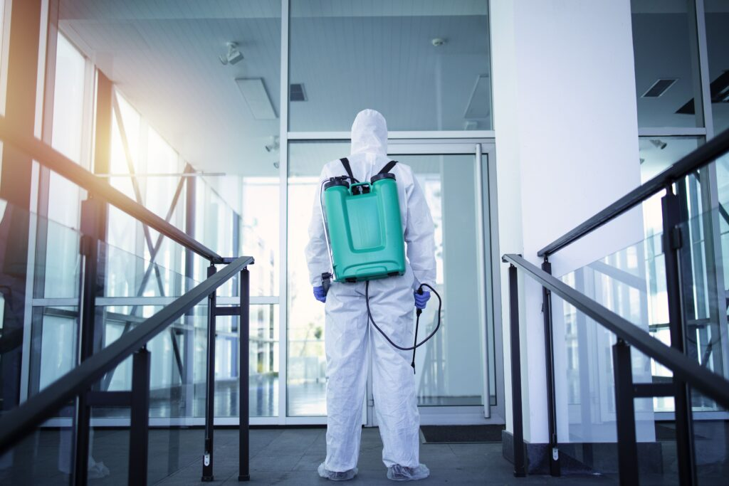 Unrecognizable Person In White Protection Suit Disinfecting Public Areas To Stop Spreading Highly Contagious Corona Virus (1)